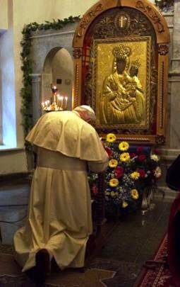 Pope Benedict XVI is kneeling before and praying to an idol of Mary.
