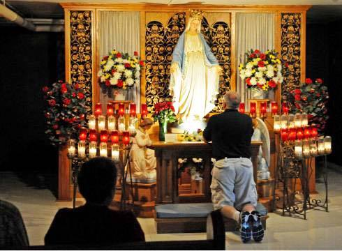 Catholic man kneels and prays in front of the Virgnin Mary