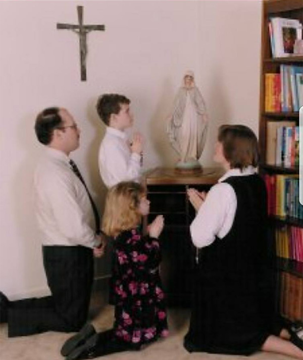 Catholic family kneels and prays in front of Mary statue