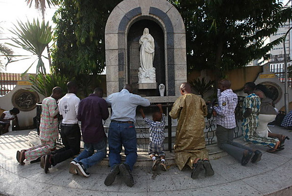 Catholic faithful pray at a statue of the Virgin Mary after a morning mass, at the Church of the Assumption in Lagos, Nigeria.